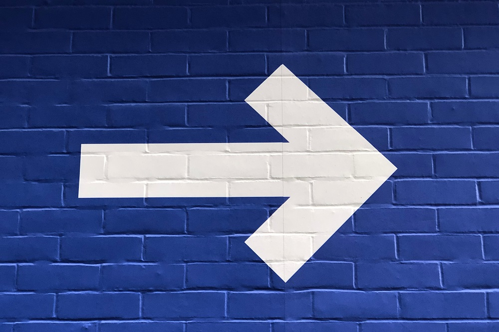 arrow pointing right on blue wall
